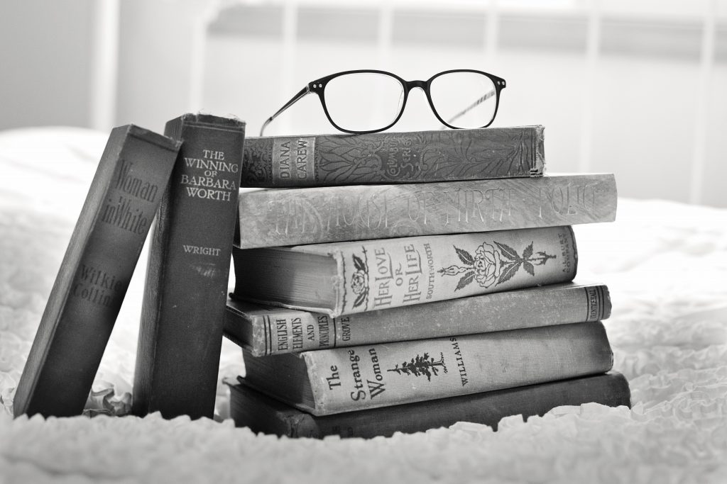 black & white picture of a stack of old books with eyeglasses sitting on top of the stack