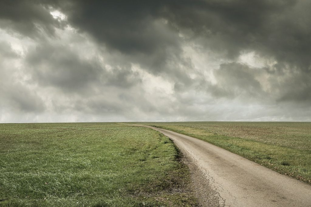road through a pasture with storm clouds in the sky