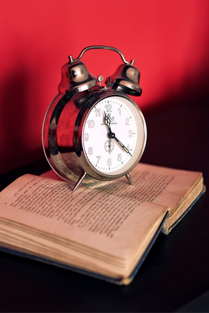 picture of a wind up clock sitting on an open book