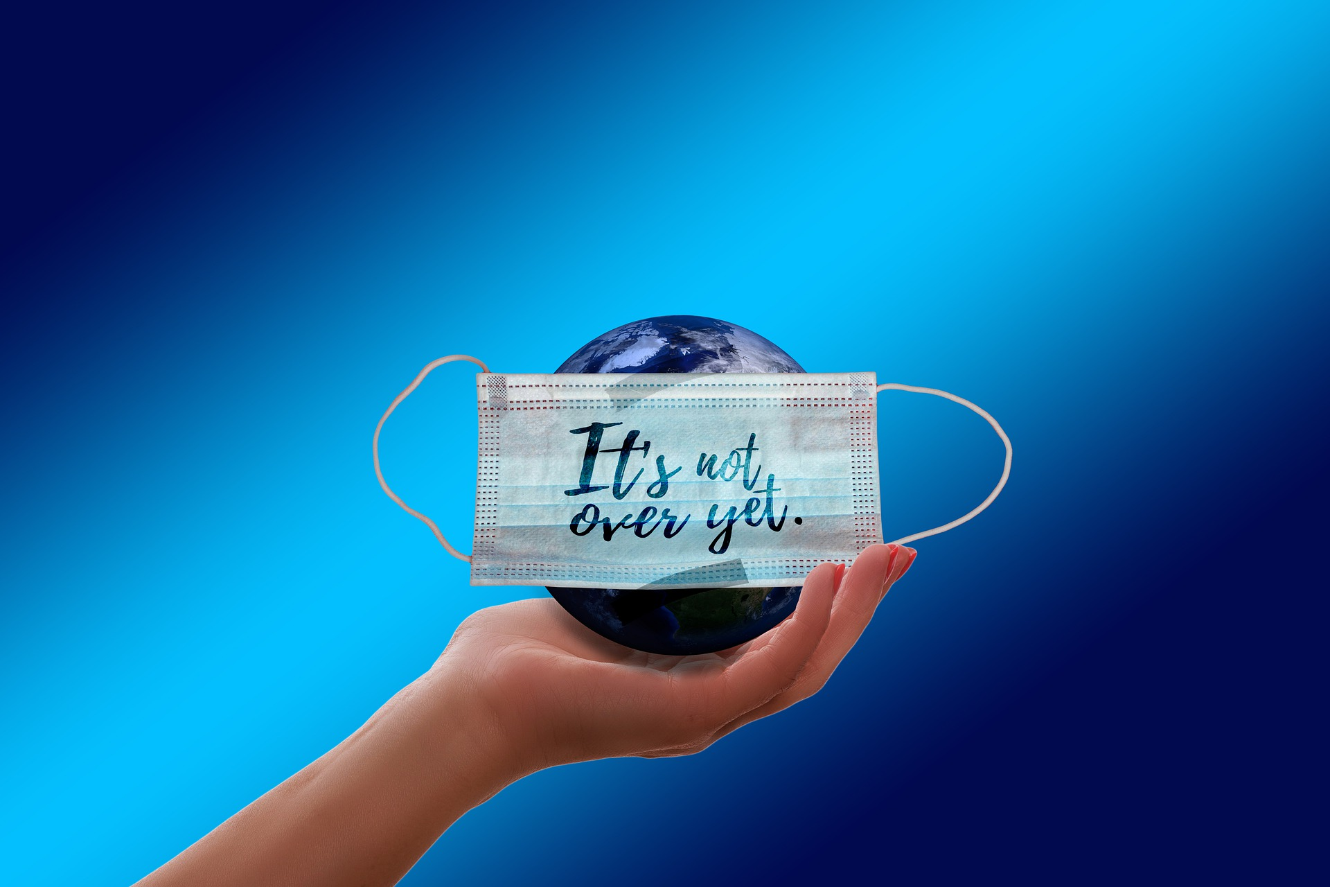 """hand holding a model earth with a mask which says """"it's not over yet"""""""